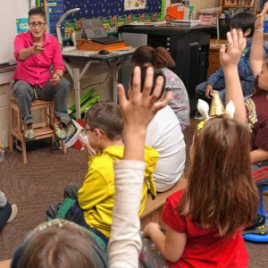 children in a classroom raising hands