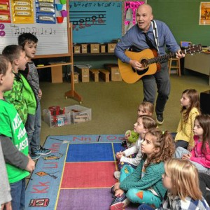 Geoffrey Gould playing guitar to school children